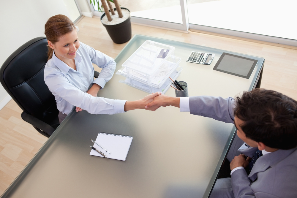 Above view of a consultant shaking hands with her client in an executive office